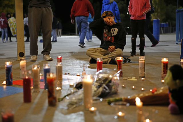 Gino Williams, 12, sits on his skateboard and wipes away tears while attending a candlelight vigil for his slain friend, Fabriccio Patti, 13, at Desert Breeze skate park in Las Vegas on Tuesday, D ...