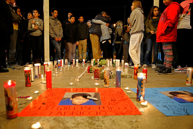 Two people embrace behind candles, flowers and memorial messages left under a gazebo at Desert Breeze skate park in Las Vegas during a vigil for Fabriccio Patti, 13, on Tuesday, Dec. 6, 2016. Patt ...