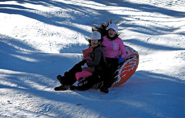 From left, Kaylee Fears, Larida Fears and Tiffany Fears get tossed into the air while sledding in Lee Canyon on Mount Charleston outside of Las Vegas Friday, Jan. 3, 2014. (John Locher/Las Vegas R ...