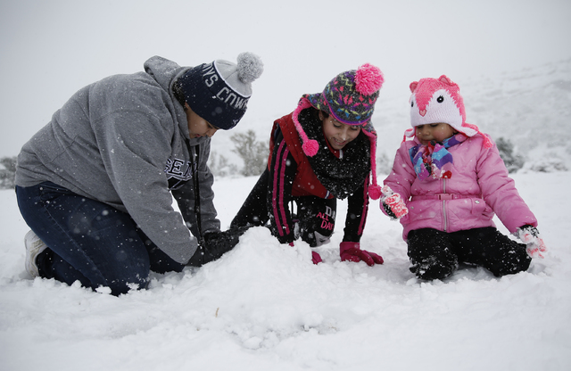 Alejandra Martinez, left, Alexis Zebaneh, 9, and Aaliyah Ortiz, 4, build a snowman outside the Spring Mountains Visitor Gateway on Saturday, Dec. 24, 2016 in Mount Charleston. (David Guzman/Las Ve ...
