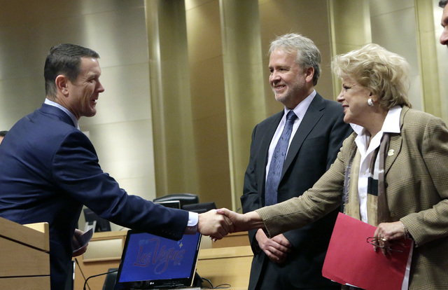 Pat Egan, NV Energy senior vice president of customer operations, left, shakes hands with Mayor Carolyn Goodman, as Tom Perrigo, planning director and chief sustainability officer at City of Las V ...