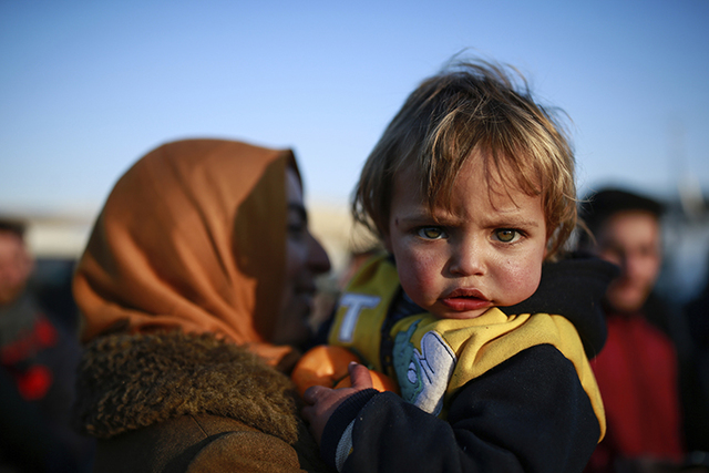 Ritach Halif, 2, is carried by her mother, after the family, which came from Idlib, Syria, crossed into Turkey at the Cilvegozu border gate with Syria, near Hatay, southeastern Turkey, Sunday, Dec ...