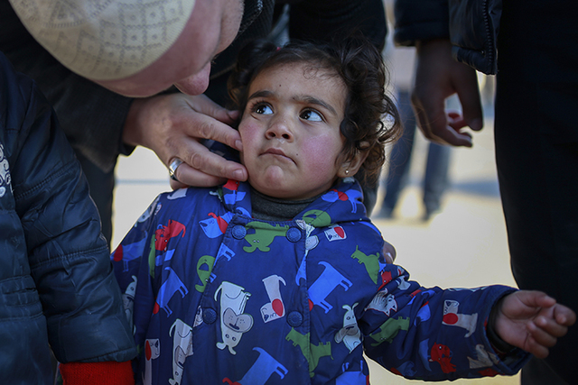 A Syrian child is comforted after she and other members of the family crossed into Turkey at the Cilvegozu border gate with Syria, near Hatay, southeastern Turkey, Sunday, Dec, 18, 2016. (Emrah Gu ...