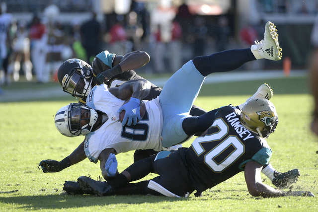 Tennessee Titans tight end Delanie Walker (82) is tackled by Jacksonville Jaguars outside linebacker Telvin Smith (50) and cornerback Jalen Ramsey (20) after catching a pass during the second half ...