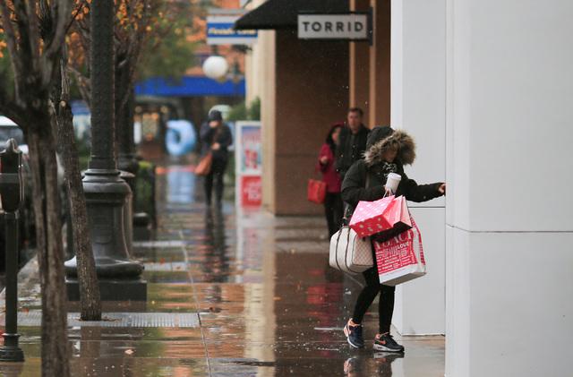A shopper ducks out of the rain into a store at Town Square in Las Vegas on Thursday, Dec. 22, 2016. Brett Le Blanc/Las Vegas Review-Journal Follow @bleblancphoto