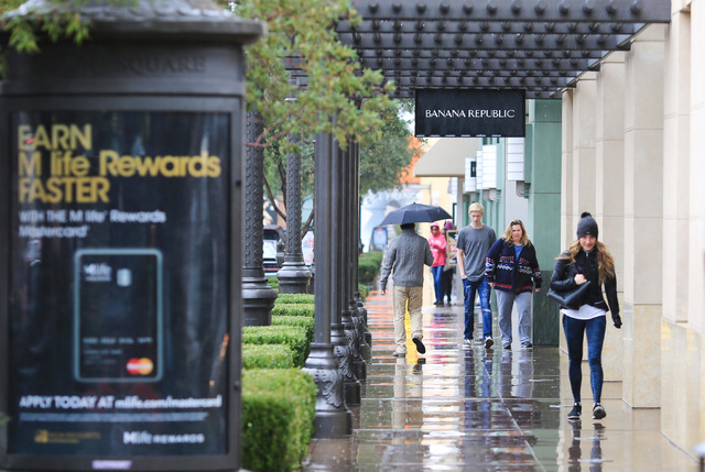 Shoppers try to stay out of the rain as the pass Banana Republic at Town Square in Las Vegas on Thursday, Dec. 22, 2016. Brett Le Blanc/Las Vegas Review-Journal Follow @bleblancphoto