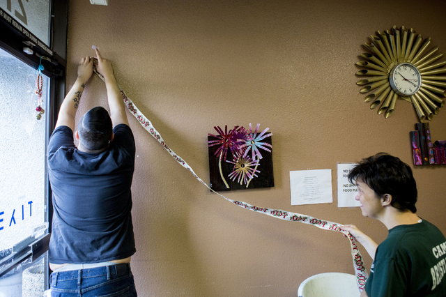 Juan Jimenez, community training specialist, left, and Debbie Jones, an individual at Transition Services facility, decorate the facility in Henderson with ribbon, Thursday, Dec. 15, 2016. (Elizab ...