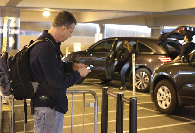 A passenger at McCarran Airport checks his phone as he waits for his ride at Ride Share pick up area Wednesday, Dec. 14, 2016, in Las Vegas. (Bizuayehu Tesfaye/Las Vegas Review-Journal)@bizutesfaye