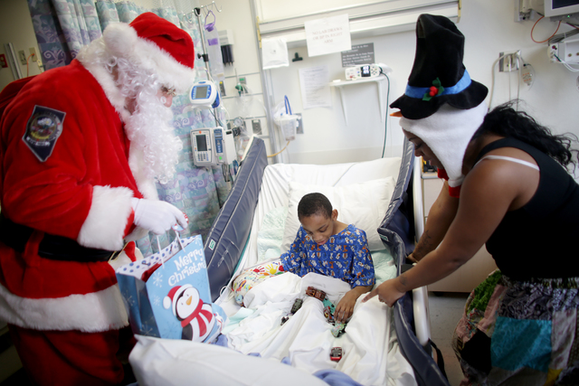 NHP Troopers and Santa Claus drop off gifts to Jeremiah, 9, at the Children's Hospital Nevada at UMC on Wednesday, Dec. 21, 2016, in Las Vegas. The NHP Trooper Santa program raises money to donate ...