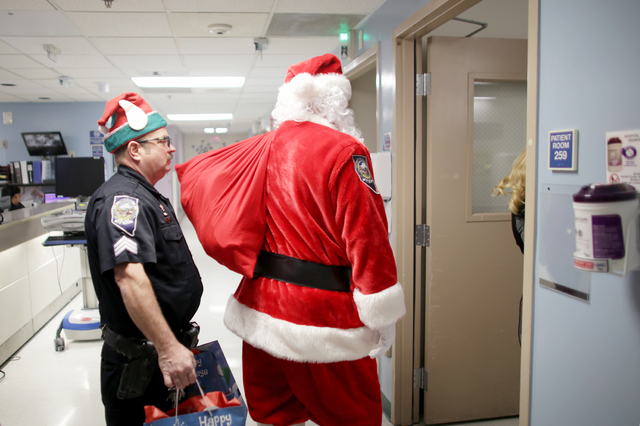 Santa Claus and NHP trooper elves enter a room to deliver gifts to children at the Children's Hospital Nevada at UMC on Wednesday, Dec. 21, 2016, in Las Vegas. The NHP Trooper Santa program raises ...