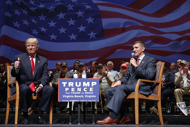 In this Sept. 6, 2016, file photo, then Republican presidential candidate Donald Trump gives a thumbs-up as he speaks with retired Lt. Gen. Michael Flynn during a town hall in Virginia Beach, Va.  ...