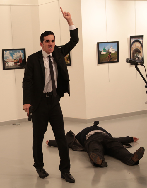 A gunman gestures near to Andrei Karlov, the Russian Ambassador to Turkey, on the ground, at a photo gallery in Ankara, Turkey, Monday, Dec. 19, 2016. An Associated Press photographer says a gunma ...