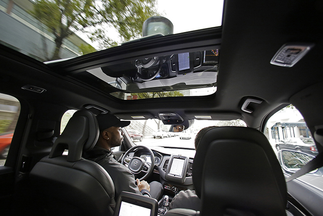 Devin Greene sits in the front seat of an Uber driverless car during a test drive in San Francisco in this file photo. Uber has pulled its self-driving cars off California roads. (Eric Risberg/AP)