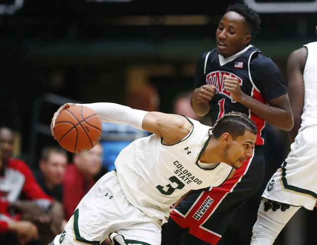 Colorado State guard Gian Clavell, front, drives to the basket past UNLV guard Kris Clyburn in the first half of an NCAA college basketball game Wednesday, Dec. 28, 2016, in Fort Collins, Colo. (A ...