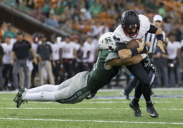 Hawaii linebacker Jahlani Tavai, left, tackles UNLV quarterback Dalton Sneed during the second quarter of an NCAA college football game, Saturday, Oct. 15, 2016, in Honolulu. (Eugene Tanner/AP)