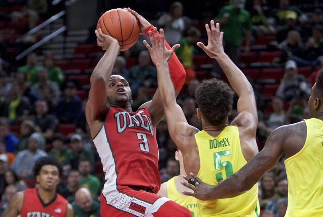 UNLV forward Tyrell Green, left, shoots over Oregon guard Tyler Dorsey during the second half of an NCAA college basketball game in Portland, Ore., Saturday, Dec. 17, 2016. (Craig Mitchelldyer/AP)