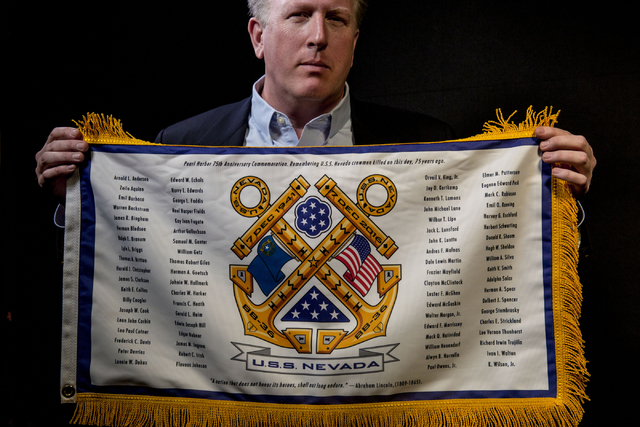 John Galloway, pilot and U.S.S. Nevada historian, holds a battle flag he designed listing the names who were killed on December 7, 1941 on the U.S.S. Nevada (BB-36), pictured at the Las Vegas Revi ...