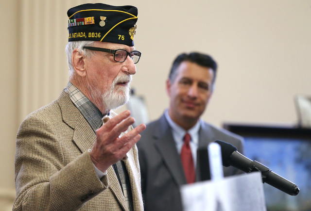 Gov. Brian Sandoval, rear, listens as Pearl Harbor survivor Charles Sehe speaks at the USS Nevada Centennial Ceremony at the Capitol in Carson City on Friday, March 11, 2016. Sehe was serving on t ...