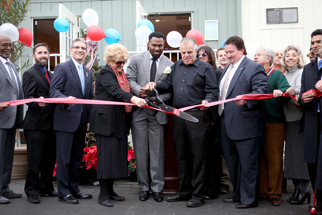Former NFL player Steven Jackson, center, cuts the ribbon for the grand opening of the second Veterans Village housing complex with the help of Mayor Carolyn Goodman and Rep. Joe Heck, at left, an ...