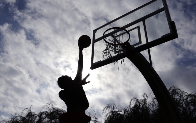 Rolando Russell of Las Vegas is silhouetted as he shoots for the basket against a cloudy sky Tuesday, Oct. 25, 2016, at Lorenzi Park in Las Vegas. (Bizuayehu Tesfaye/Las Vegas Review-Journal Follo ...