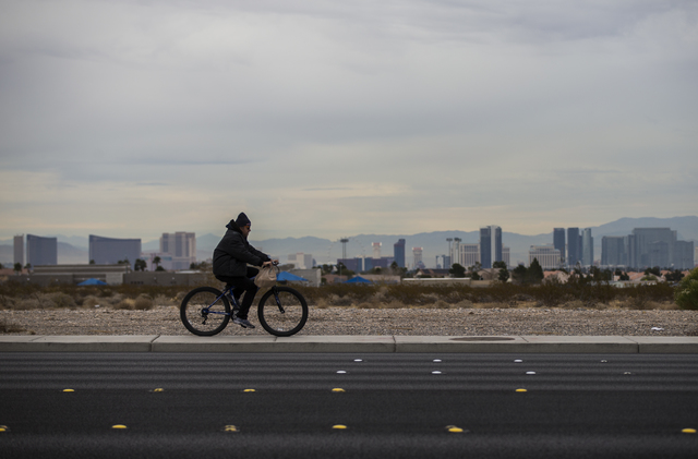 A cyclist on Durango Road with a view of the Strip in Las Vegas on Friday, Dec. 30, 2016. (Chase Stevens/Las Vegas Review-Journal) @csstevensphoto