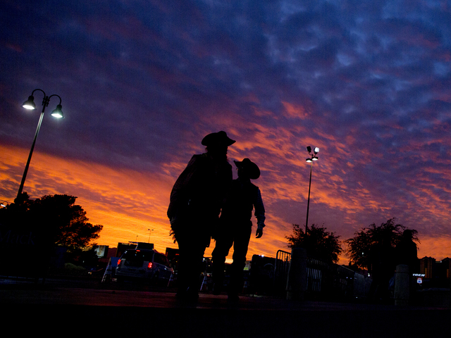 Attendees of the National Finals Rodeo walk into the Thomas & Mack Center at dusk on Monday, Dec. 5, 2016, in Las Vegas. (Benjamin Hager/Las Vegas Review-Journal)