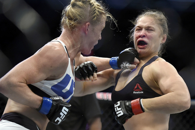 Holly Holm, left, punches Ronda Rousey Nov. 15, 2015, during their UFC 193 bantamweight mixed martial arts title fight in Melbourne, Australia. (Andy Brownbill/File, AP)