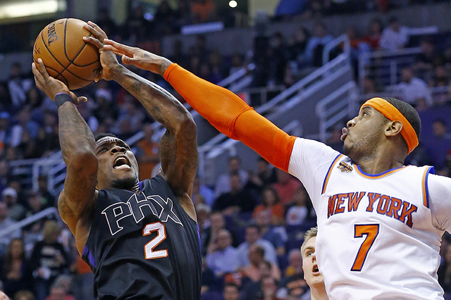 New York Knicks forward Carmelo Anthony (7) defends on a shot by Phoenix Suns guard Eric Bledsoe (2) during the second half of an NBA basketball game Tuesday, Dec. 13, 2016, in Phoenix. The Suns d ...