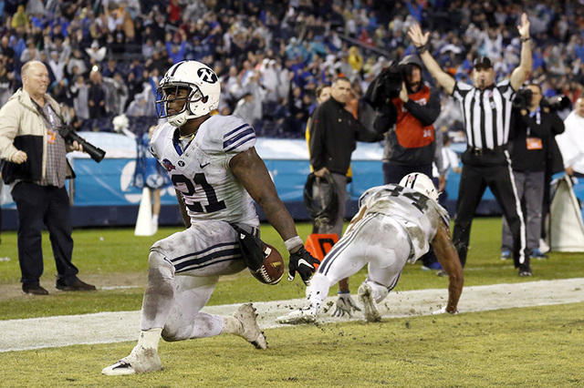 BYU running back Jamaal Williams, left, scores a touchdown against Wyoming during the first half of the Poinsettia Bowl NCAA college football game Wednesday, Dec. 21, 2016, in San Diego. (AP Photo ...