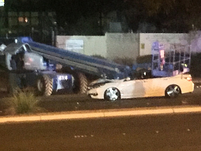 A crane landed on a white Honda just after 6:20 p.m. when the crane was being towed on Charleston Boulevard near Hualapai Way. (Marian Green/Las Vegas Review-Journal)