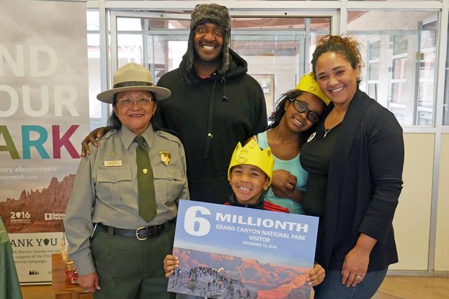 Las Vegas couple James and Abigail Johnson and their children, Sophia and Elijah, pose Monday with a National Park Service employee after being named the record 6th million visitors to Grand Canyo ...