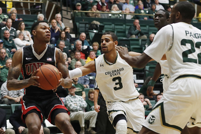 UNLV forward Troy Baxter Jr., left, looks to pass the ball as Colorado State guards Gian Clavell, center, and J.D. Paige defend during the first half of an NCAA college basketball game Wednesday,  ...