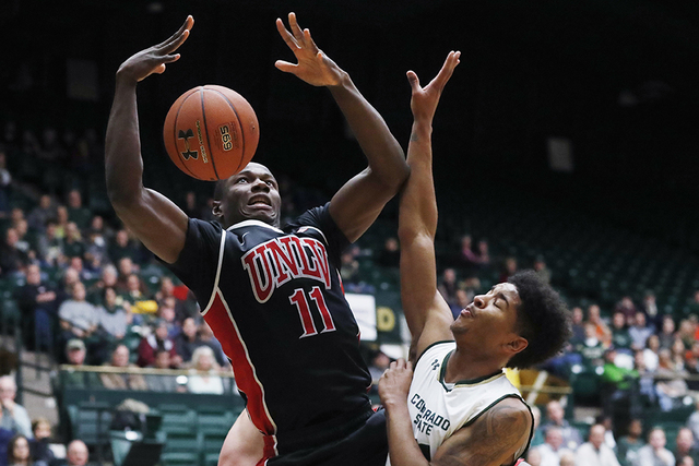UNLV forward Cheickna Dembele, left, is fouled by Colorado State forward Braden Koelliker, back, as guard Prentiss Nixon defends during the first half of an NCAA college basketball game Wednesday, ...