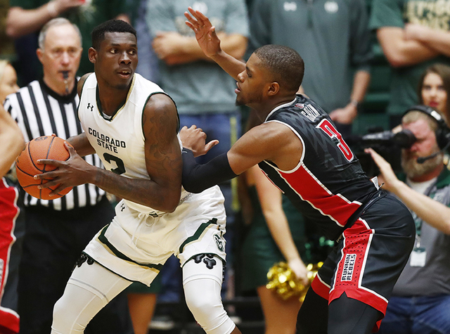 Colorado State forward Emmanuel Omogbo, left, looks to pass the ball as UNLV forward Tyrell Green defends during the second half of an NCAA college basketball game Wednesday, Dec. 28, 2016, in For ...