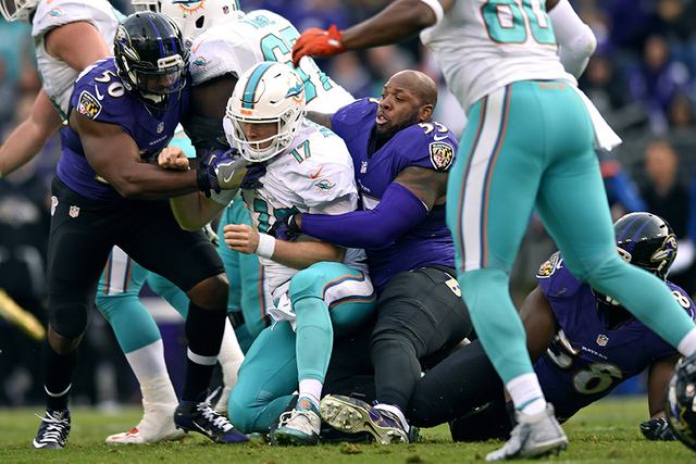 Baltimore Ravens outside linebacker Terrell Suggs (55) tackles Miami Dolphins quarterback Ryan Tannehill after his helmet fell off in the second half of an NFL football game, Sunday, Dec. 4, 2016, ...