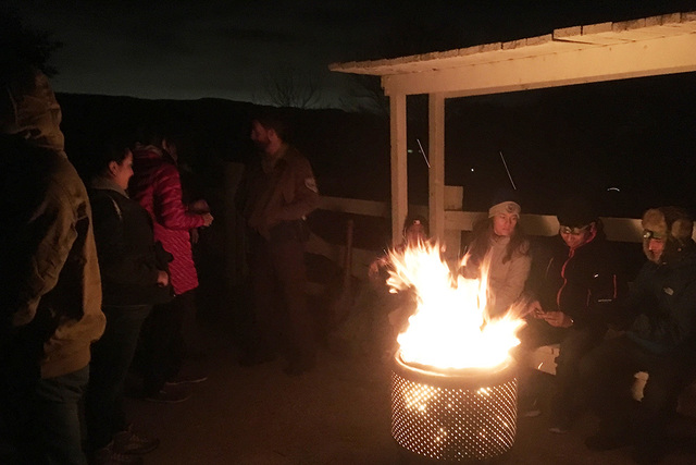 Hikers gather around a fire before departing on a 2-mile trek. BRIAN SANDFORD/VIEW