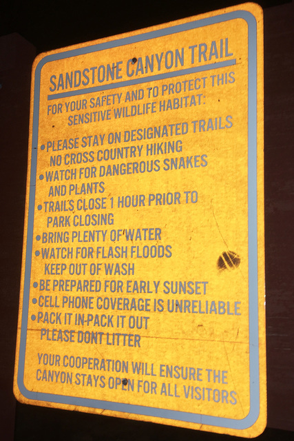 A sign warning hikers is illuminated by a camera flash in the darkness. BRIAN SANDFORD/VIEW