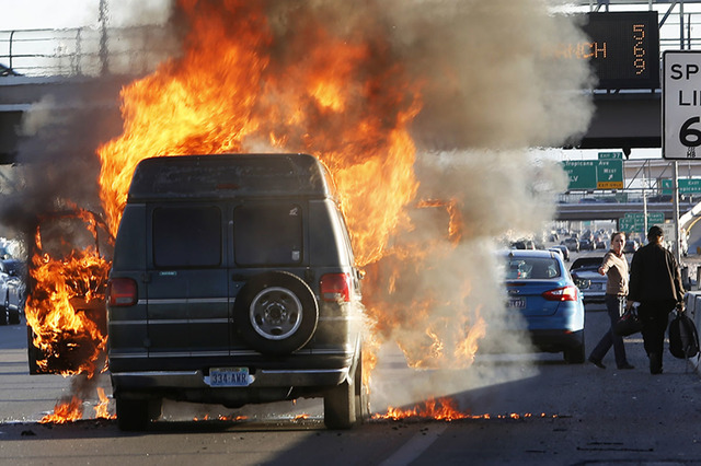 A passenger flees from his vehicle while it is engulfed in flames on I-15 south near exit 37 on Saturday, Jan. 28, 2017, in Las Vegas.