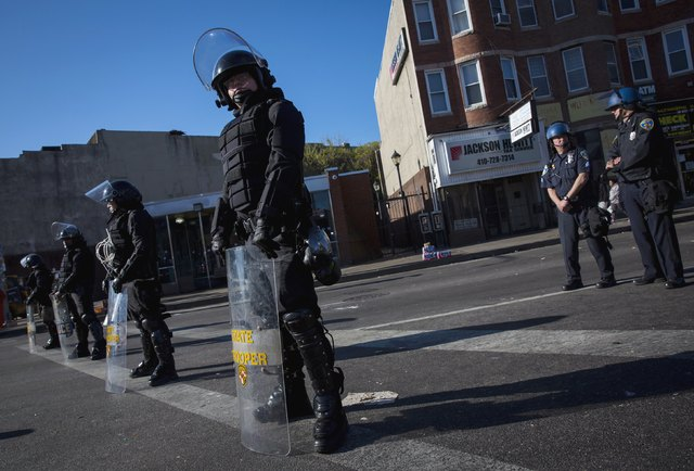 Maryland State Police stand guard in Baltimore, April 28, 2015. Baltimore erupted in violence on Monday as hundreds of rioters looted stores, burned buildings and at least 15 police officers were  ...