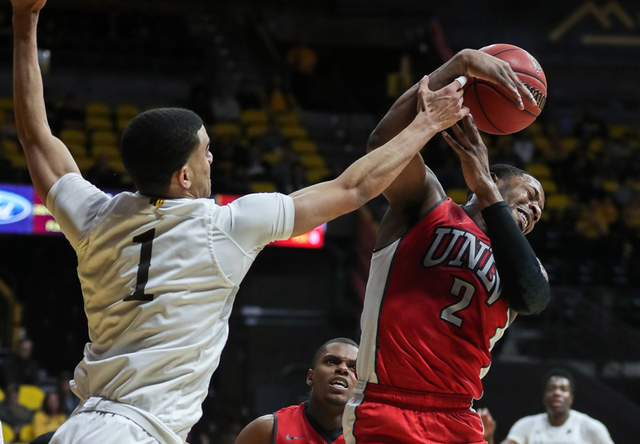 UNLV Runnin' Rebels guard Uche Ofoegbu (2) grabs a rebound against Wyoming Cowboys guard Justin James (1) during the second half at Arena-Auditorium. The Cowboys beat the Rebels 66-65. (Troy Babbi ...