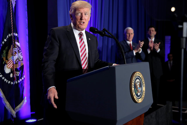 President Donald Trump is applauded by Vice President Mike Pence and House Speaker Paul Ryan, R-Wisc., as he arrives to speak at a congressional Republican retreat in Philadelphia, Jan. 26, 2017.  ...