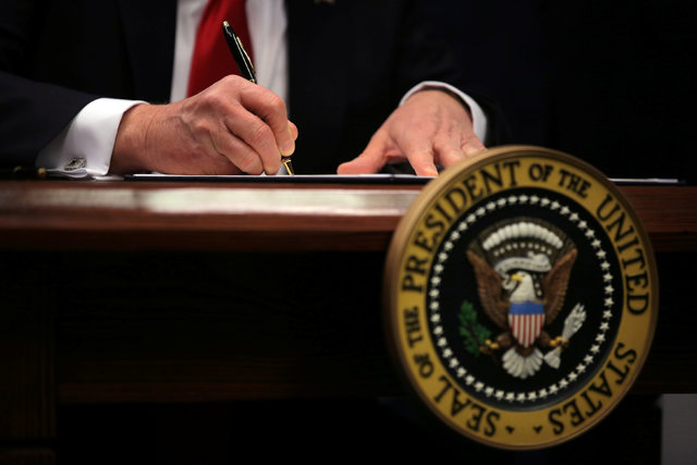 "U.S. President Donald Trump signs an executive action he said would begin the rebuilding of the U.S. military by ""developing a plan for new planes, new ships, new resources and new tools for our m ..."