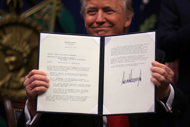 "U.S. President Donald Trump shows an  executive action he said would begin the rebuilding of the U.S. military by ""developing a plan for new planes, new ships, new resources and new tools for our  ..."