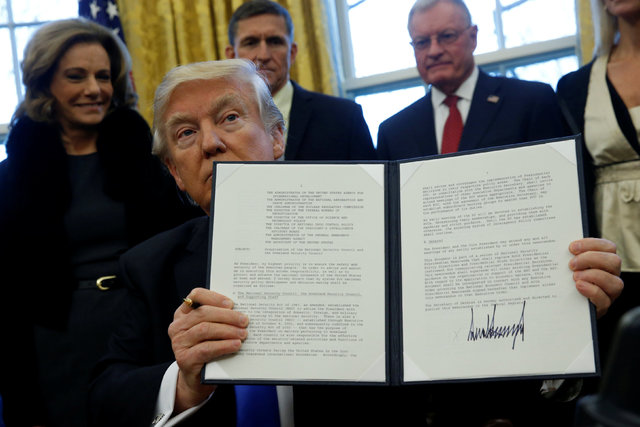 U.S. President Donald Trump holds an executive order dealing with the structure of the National Security Council after signing it in the Oval Office at the White House in Washington, U.S. January  ...