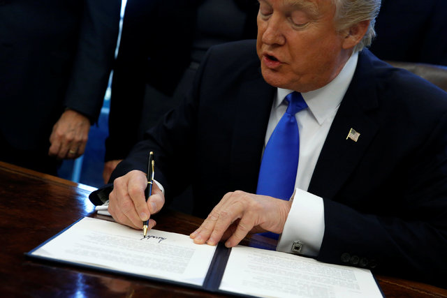 U.S. President Donald Trump signs an executive order dealing with the structure of the National Security Council, in the Oval Office at the White House in Washington, U.S. January 28, 2017. REUTER ...