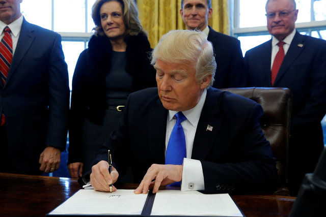 U.S. President Donald Trump signs an executive order dealing with members of the administration lobbying foreign governments, in the Oval Office at the White House in Washington, U.S. January 28,  ...
