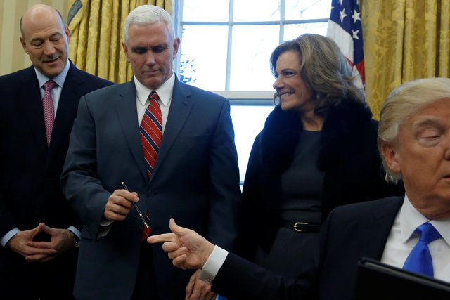 U.S. President Donald Trump hands the pen to Vice President Mike Pence after signing an executive order dealing with the structure of the National Security Council, in the Oval Office at the White ...