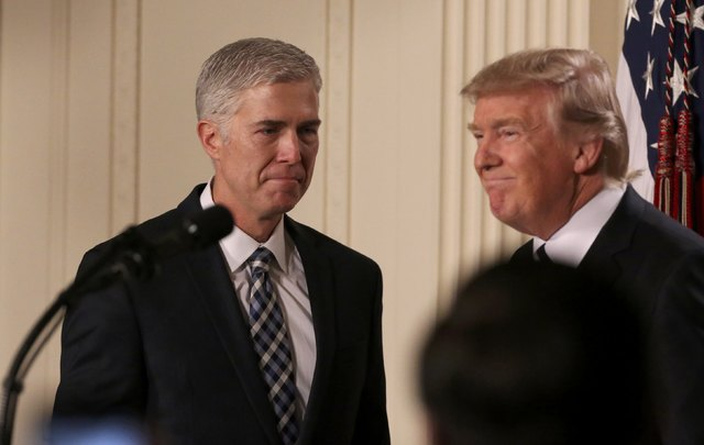 U.S. President Donald Trump looks on as Neil Gorsuch (L) approaches the podium after being nominated to be an associate justice of the U.S. Supreme Court at the White House in Washington, D.C., U. ...