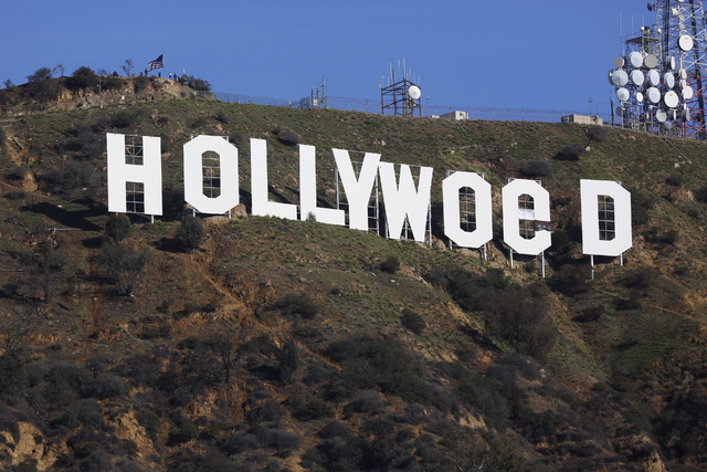 Los Angeles County firemen remove banners from the letters on the Hollywood sign, seen vandalized Sunday, Jan. 1, 2017. Los Angeles residents awoke New Year's Day to find a prankster had altered t ...