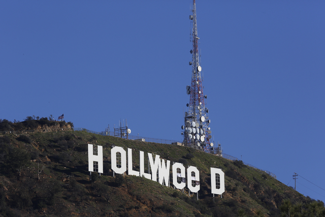 "The Hollywood sign is seen vandalized, Sunday, Jan. 1, 2017. Los Angeles residents awoke New Year's Day to find a prankster had altered the famed Hollywood sign to read ""HOLLYWeeD."" (Damian Dovarg ..."